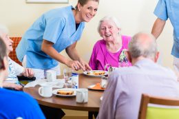 61779241 - group of seniors having food in nursing home, a nurse is serving